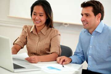 Multi ethnic coworkers couple working on documents