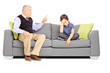 Angry granddad shouting at his sad nephew, seated on a sofa
