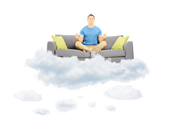 Young male meditating on a sofa and floating on a cloud