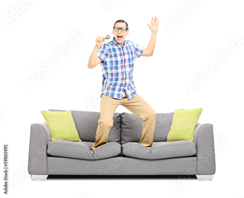 Smiling guy with microphone singing and standing on a sofa