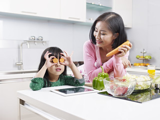 asian mother and daughter playing in kitchen
