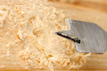 Close-up image of drilling hole on wooden plank