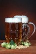 Glasses of beer and hops, on wooden table