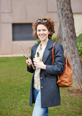 Female redhead student carrying notebook and coffee to go