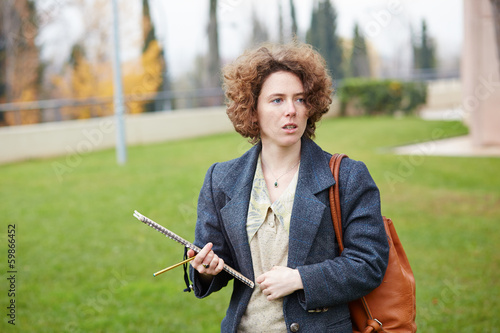 Female redhead student carrying notebook
