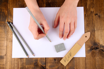 Hands with art materials on wooden background