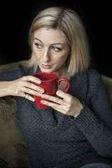 Blonde Woman with Beautiful Blue Eyes and Red Coffee Cup.