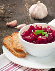 Beetroot salad with garlic in a white bowl