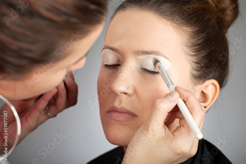 Make-up artist applying white eye shade