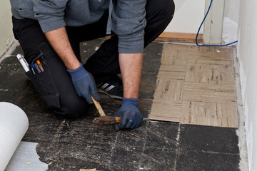 Builder lifting old floor tiles in a passage