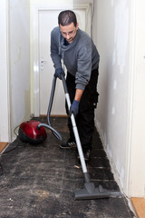 Workman vacuuming a passage during renovations