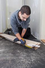 Carpenter measuring new wooden floor boards