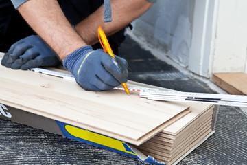 Carpenter measuring new wooden flooring