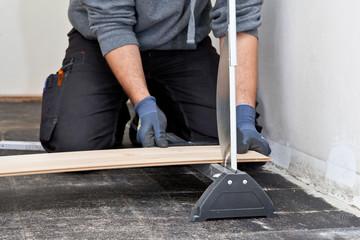 Carpenter cutting a floor board for installation