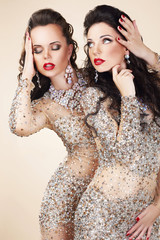 Two Glamorous Women in Evening Dresses and Jewelry Dancing