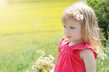 Baby girl among rapeseed field with camomile bouquet