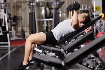Athletic man working his chest with heavy dumbbells