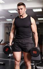 Athletic man holding heavy dumbbells