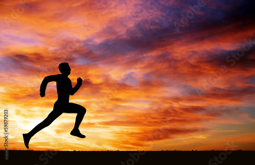 Silhouette of running man on sunset fiery background