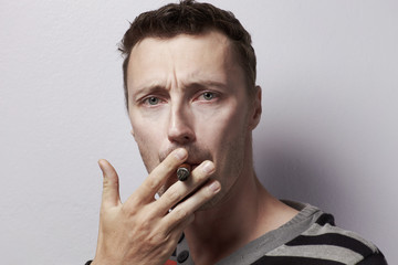 Caucasian man portrait with cigar in studio