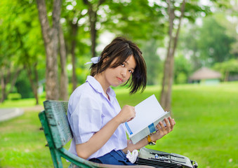 Cute Thai schoolgirl is studying on a bench and smiling