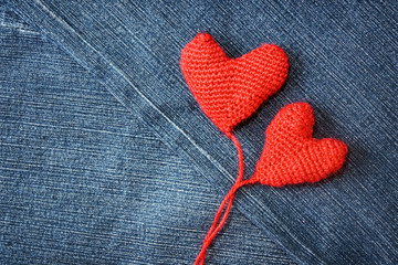 Knitted heart on blue jeans texture background