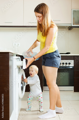 Family using washing machine with laundry