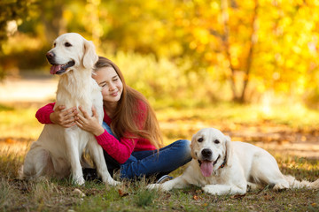 Beautiful woman and her dog posing in autumn park