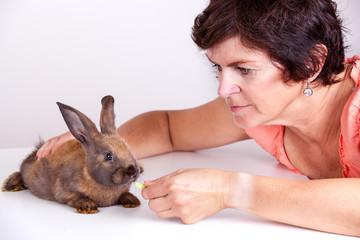 Young woman feeding rabbits