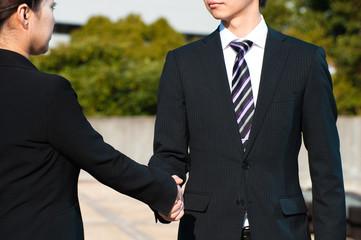 スーツ姿で握手する二人