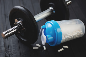 Dumbbell and shaker with capsules, horizontal shot