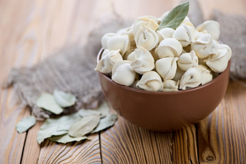 Bowl of raw pelmeni with bay leaves on a wooden table