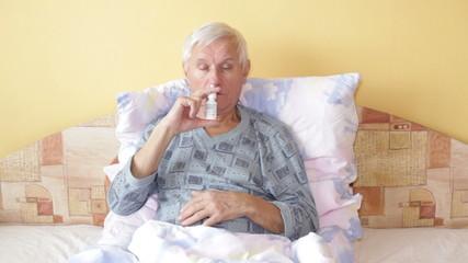 Ill senior man using nasal spray in bed.