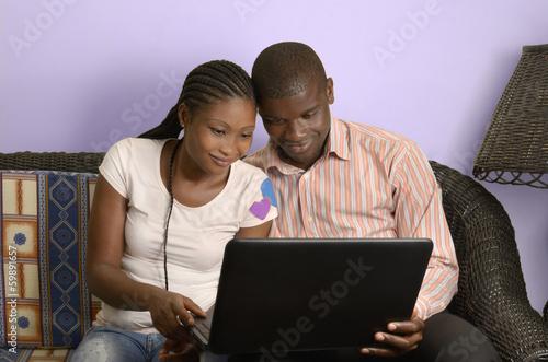 canvas print picture Junges afrikanisches Paar surft im Internet