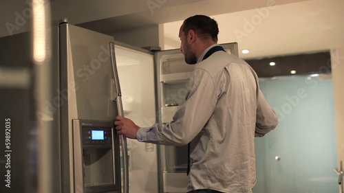 Young businessman taking apple from the fridge