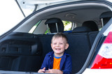 Laughing little boy sitting in the back of a car