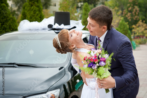 bride and groom around a decorated car