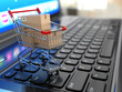canvas print picture - E-commerce. Shopping cart with cardboard boxes on laptop.