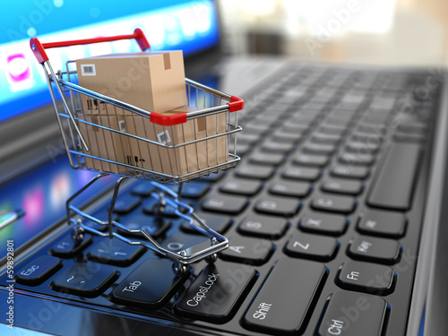 canvas print picture E-commerce. Shopping cart with cardboard boxes on laptop.