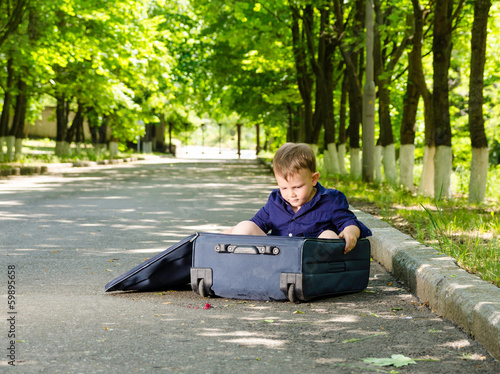 Young boy playing with an open suitcase