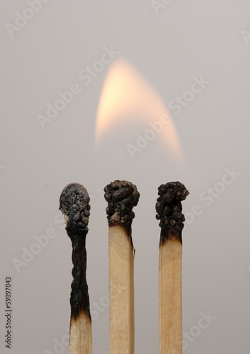 three lighted matches on gray background