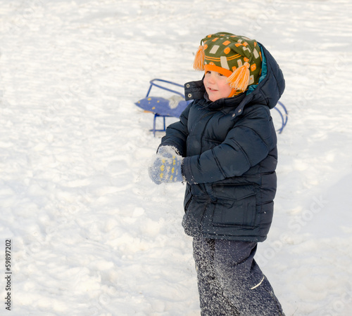 Little boy playing in the snow