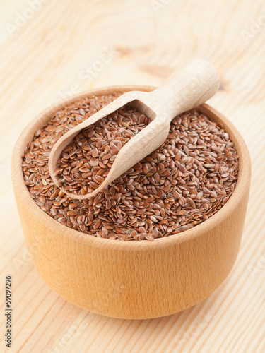 linseed, flax seeds with wooden scoop in mortar