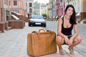 Young woman crouching alongside a suitcase