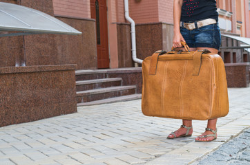 Woman waiting with her suitcase in the street