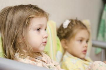 двое детей сидят на диване и смотрят направо