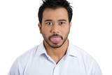Funny, unhappy young man sticking out his tongue