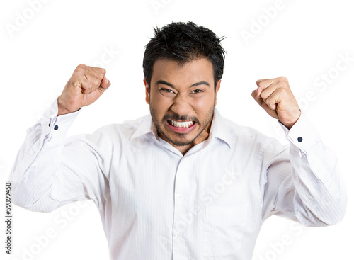Angry, upset, mad young man with fists in the air, screaming