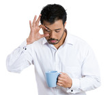 Sleepy business man holding cup of coffee, trying to stay awake