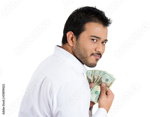Greedy young business man holding tightly dollar bills